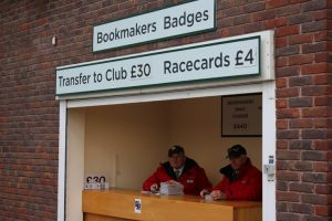 bookmaker badges and race cards stand at cheltenham racecourse