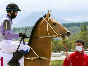 jockey on horse wearing face mask