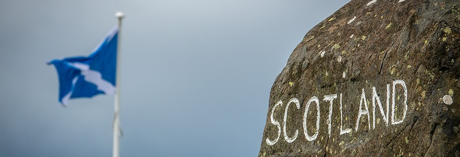 scotland written on stone with flag in background
